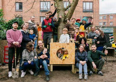 Co-DB, parents and children of Grasshoppers nursery power pose on the newly built treehouse.
